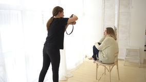 Young female photographer taking picture of smiling model in white jumper and dark jeans which are sitting on the wooden stock photography
