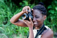 Young female photographer taking pictures. Travel, tourism and hobby. Young woman photographer taking pictures in the bush stock photo