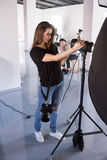 Young female photographer work in studio. Beautiful women with camera is setting photographing equipment in studio getting ready for a photo shoot stock photography