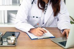 Young female physician using laptop royalty free stock image