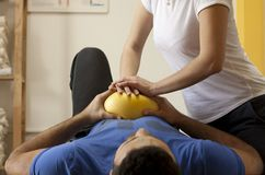 Rehabilitation practice with ball. Ball against chests. Young female physiotherapist training with colleague. Practice hand therapy with yellow ball. Hands Stock Images