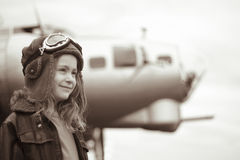 Young female pilot looking into distance. Young female pilot is looking off into the distance, wearing flight jacket/hat/goggles.  Bomber is out of focus in the Royalty Free Stock Images