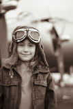 Young female pilot smiling at the camera. Young female pilot is smiling at the camera, wearing flight jacket/hat/goggles.  Bomber is out of focus in the Royalty Free Stock Image