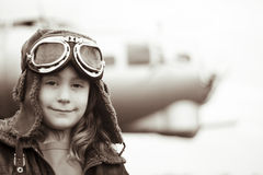 Young female pilot smiling at the camera. Young female pilot is smiling at the camera, wearing flight jacket/hat/goggles.  Bomber is out of focus in the Royalty Free Stock Photos