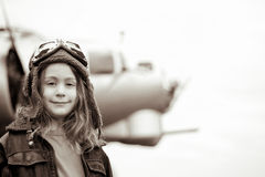 Young female pilot smiling at the camera. Young female pilot is smiling at the camera, wearing flight jacket/hat/goggles.  Bomber is out of focus in the Stock Photos