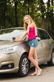Cute girl with paper cup near car stock images