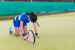 Young female player is upset and  fell on her knees because of t. Young female player wearing a sportswear is upset and  fell on her knees because of the loss in Stock Photo