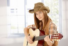 Young female playing guitar in western style Royalty Free Stock Photography