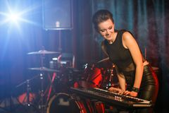 Young female playing keyboards on stage. Young female playing keyboards on empty stage Royalty Free Stock Photo