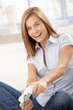 Young female playing video game smiling Stock Photography