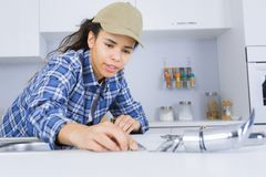 Young female plumber working on sink royalty free stock image