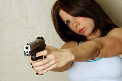 Young female pointing a gun. Close up image of young attractive female pointing gun at someone breaking and entering Royalty Free Stock Images