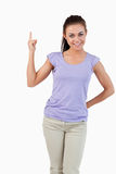 Young female pointing upwards while smiling Stock Images