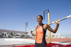 Young female pole vault athlete with pole by bar, smiling, portrait Stock Images
