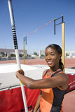 Young female pole vault athlete with pole by bar, smiling, portrait Royalty Free Stock Photo