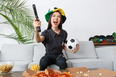 Young woman police officer sport fan watching match holding gun and ball stock image