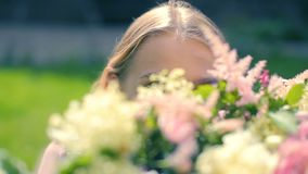 Young female plays to the camera stare down Looking through flowers decoration in the green magic grassy garden courses stock video footage