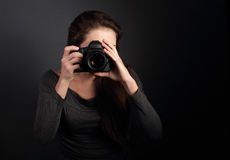 Young female potograph making the photo on dark background holdi Royalty Free Stock Photos