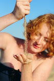Young female pouring sand hand to hand. Young red haired female pouring sand from hand to hand on a beach Royalty Free Stock Images