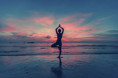 young female practicing yoga on the beach at sunset Royalty Free Stock Photo