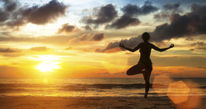 Young female practicing yoga on the sea beach at sunset. Stock Image