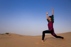 Young female practising yoga pose Warior or Virabhadrasana Royalty Free Stock Photos