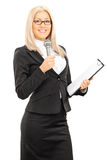 Young female presenter holding microphone and clipboard Stock Photos
