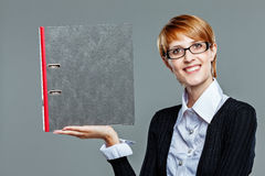 Young female presenting a folder smiling friendly to the camera Stock Photos