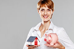 Young female presenting a model house and a piggy bank Stock Image