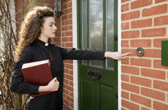 Young female priest making a house call Stock Photos