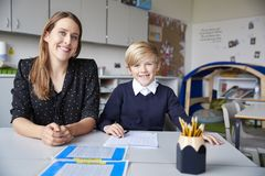 Young female primary school teacher and schoolboy sitting at a table, working one on one in a classroom, smiling to camera, front stock photos