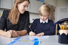 Young female primary school teacher and schoolboy sitting at a table working one on one, looking down, front view, close up stock image