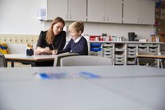 Young female primary school teacher and schoolboy sitting at a table working one on one, selective focus royalty free stock photography
