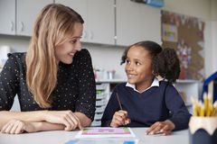 Young female primary school teacher working one on one with a schoolgirl at a table in a classroom, both looking at each other smi. Ling, close up royalty free stock images