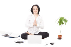Young female professional resting in lotus pose in front of lapt Stock Images