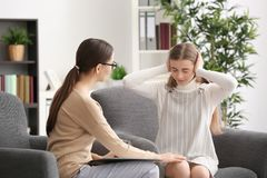 Young female psychologist working with teenager  girl in office. Young female psychologist working with teenager girl in office Royalty Free Stock Photo