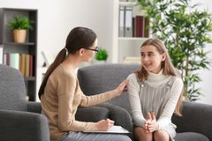 Young female psychologist working with teenager girl in  office. Young female psychologist working with teenager girl in office Royalty Free Stock Image