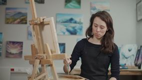 Woman is drawing a picture in master class of painting in studio. Young female pupil artist is painting a picture in class. She is standing in front of easel and stock video
