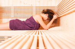 Young female in purple towel relaxing in wooden sauna Royalty Free Stock Photo
