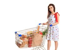 A young female pushing a shopping cart full with groceries isolated on white background. Brunette in a summer dress makes purchases Stock Photography