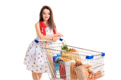 A young female pushing a shopping cart full with groceries isolated on white background. Brunette in a summer dress makes purchases Stock Image