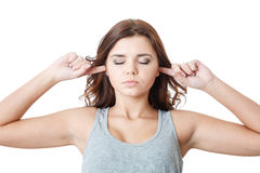 Young female putting fingers in ears Stock Images