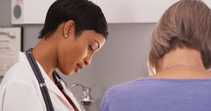 Young female radiologist with senior female patient looking x-ra Stock Photo