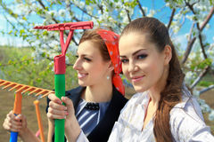Young female with rakes Royalty Free Stock Photo