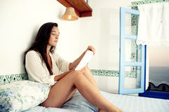 Young female reading book on bed Stock Photos