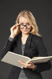 Young female reading book through eyeglasses Stock Image