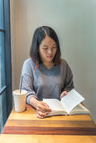 Young female reading a book at the library Stock Photos