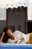 Young female reading a book. While lying on bed as seen from an open window of a traditional country house Royalty Free Stock Photography