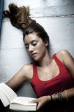 Young female reading book. While lying on floor Stock Photography