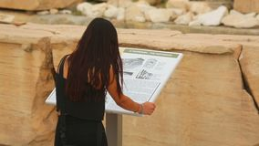 Young female reading information about Parthenon temple on tourist guide table. Stock footage stock footage